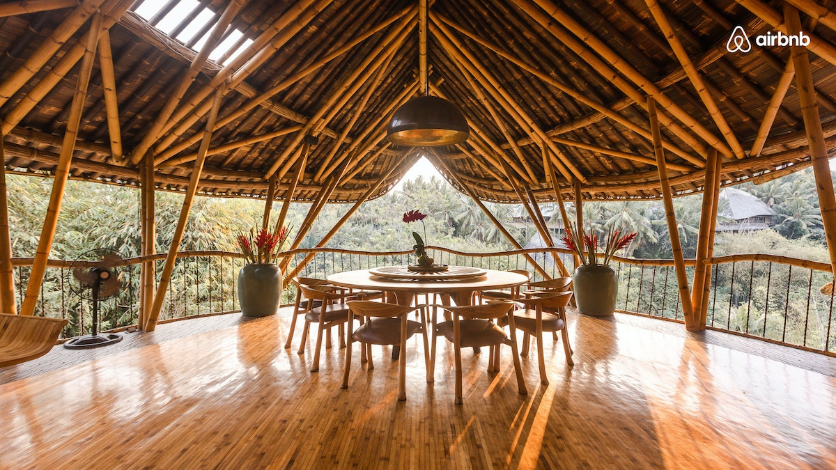 A bamboo house in Bali, Indonesia has a round table with chair all around, overlooking nature.
