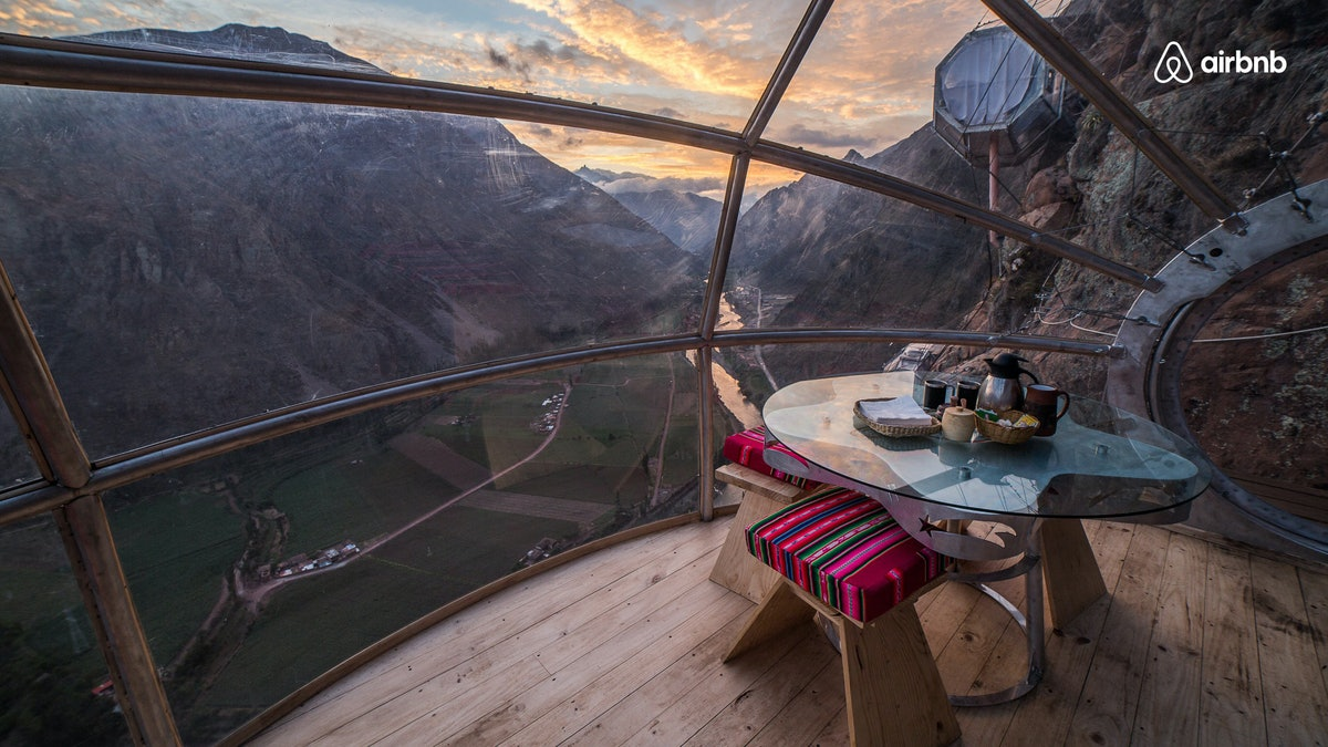 A skylodge in Peru is high above the ground in the mountains, with windows all around so you can see the sunset.