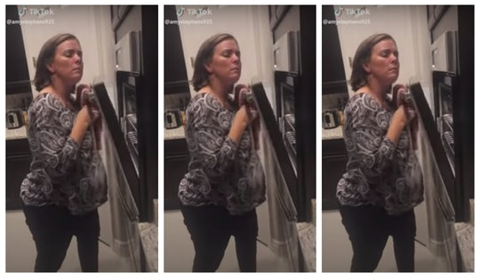 A mom creaks an oven for for a tiktok video