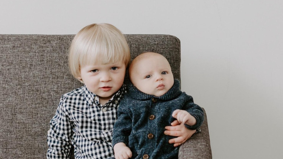 A brother holds his baby sibling