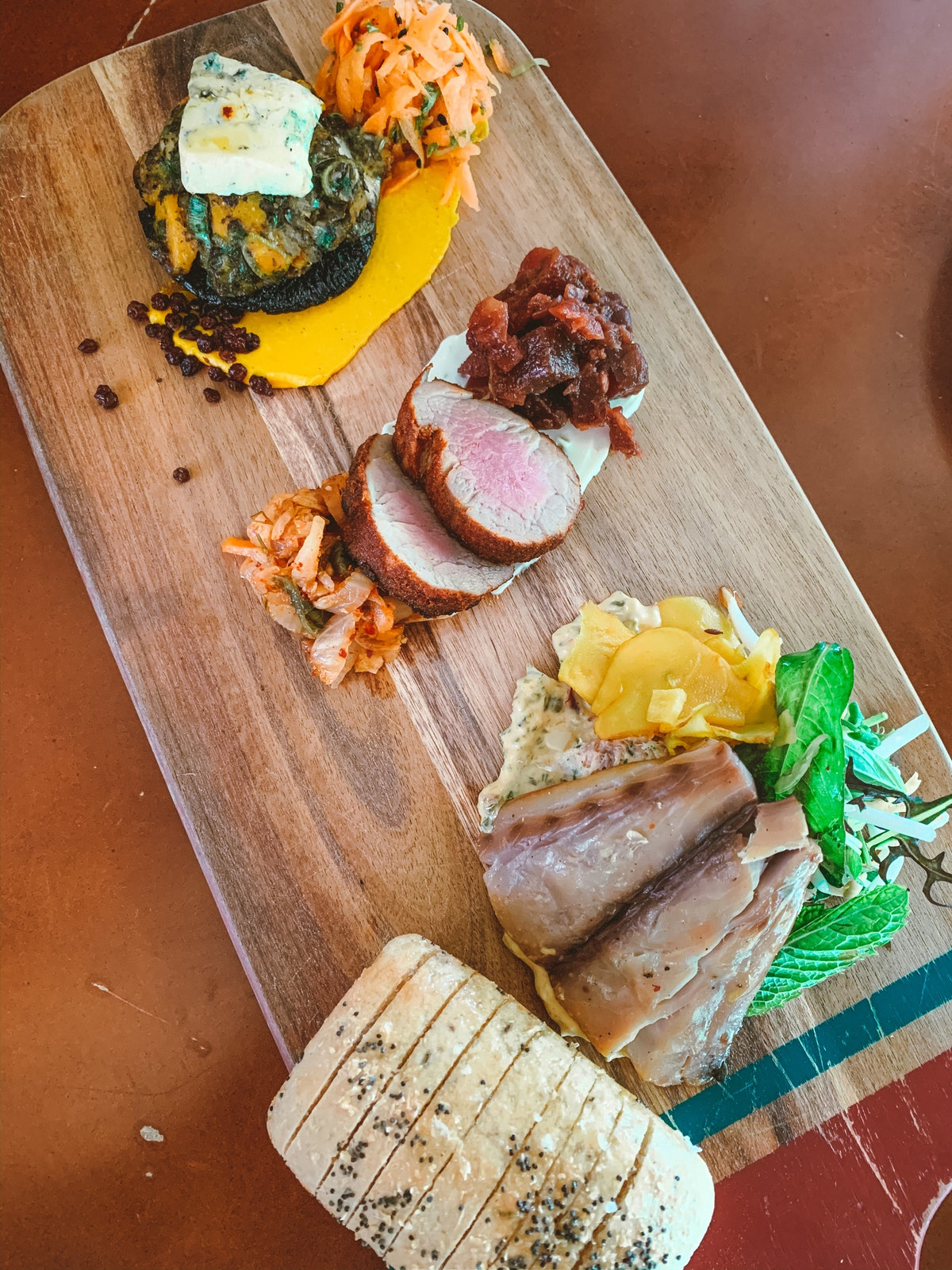A wooden platter of food sits on the table.