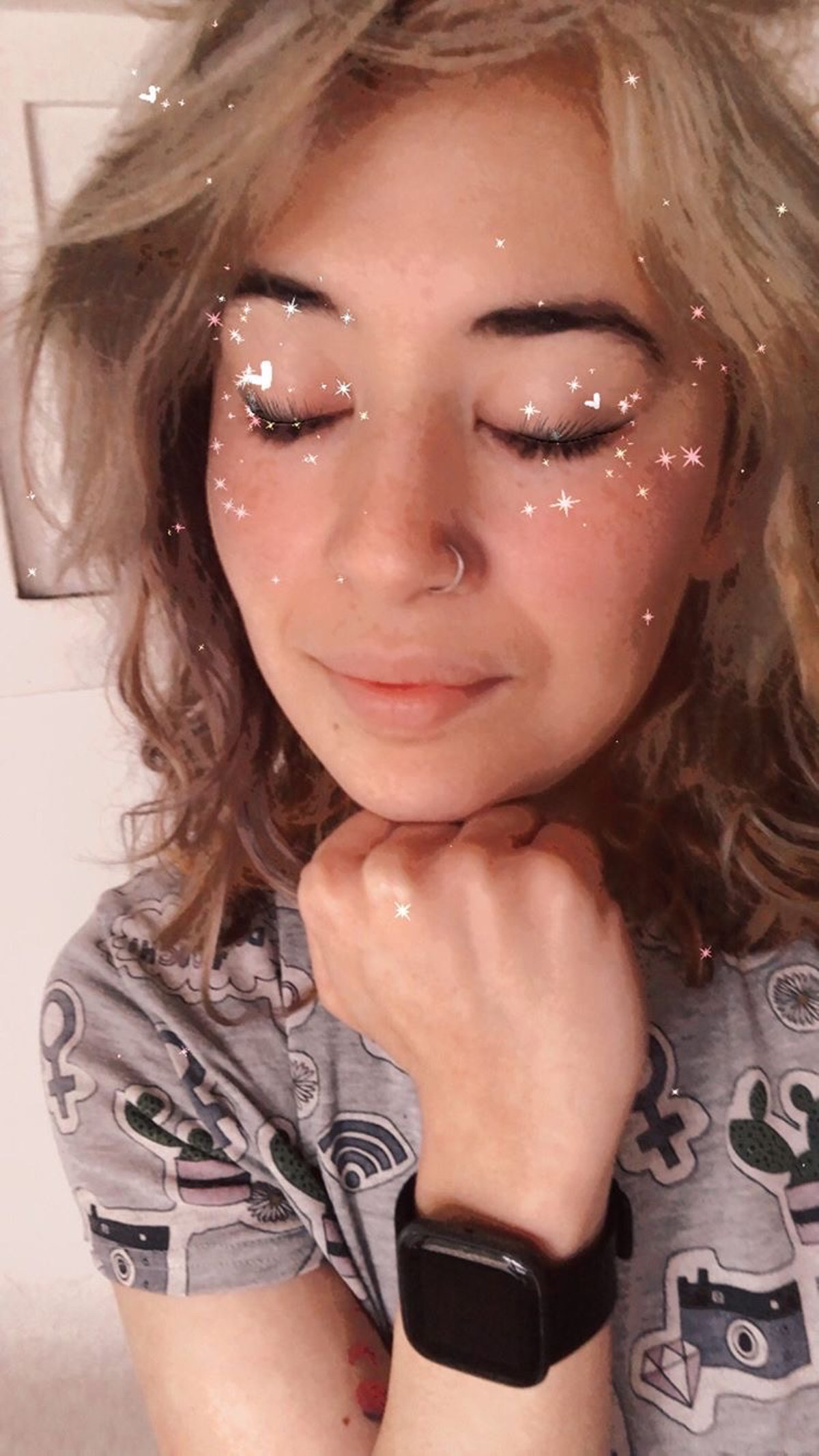 A woman closes her eyes with glitter filtered all around her face.