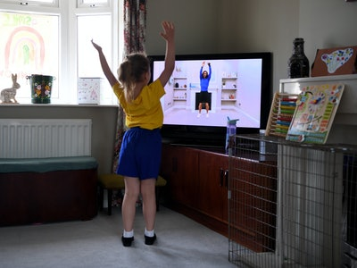 A girl exercises along with her teacher through a screen