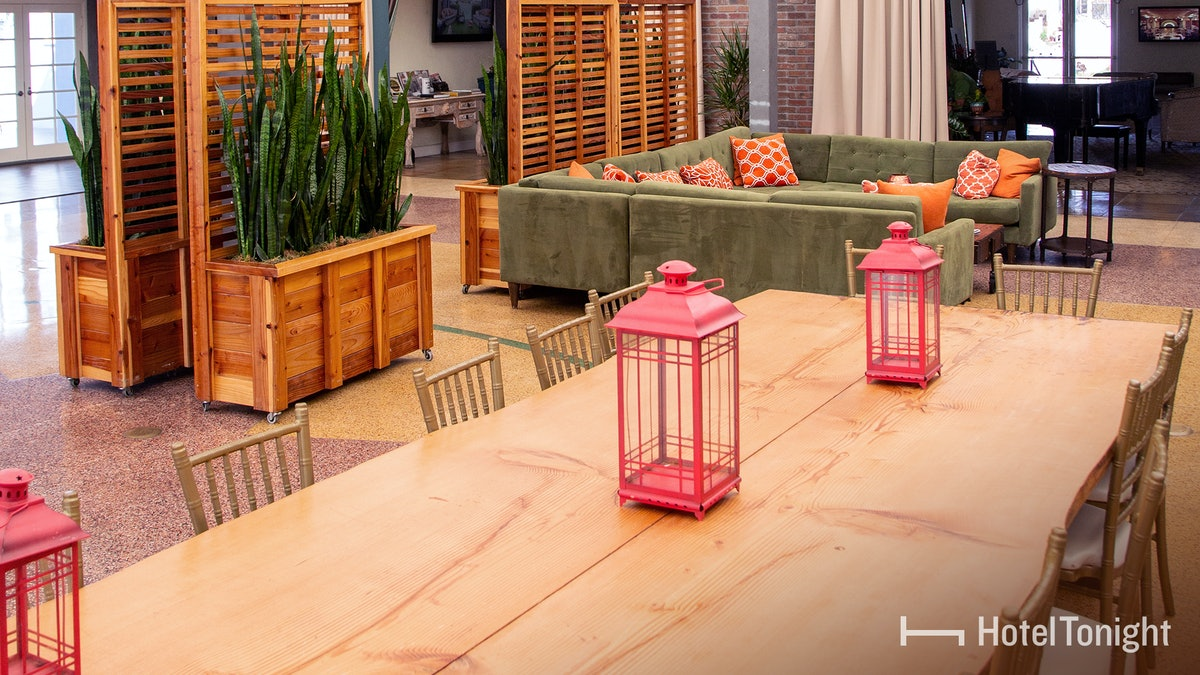 A large dining table in a hotel in San Diego, California has red lanterns on it and minimalistic chairs.