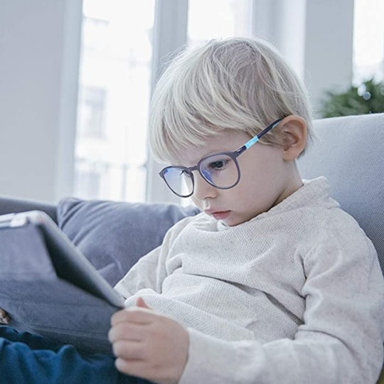 Little boy looking down at a tablet while wearing blue light blocking glasses