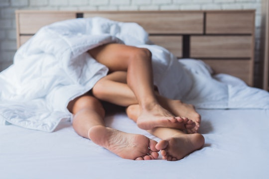 closeup of couples' feet in bed