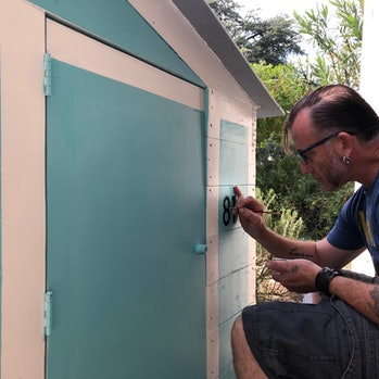 Gano painting the house.