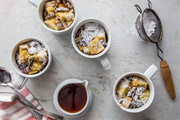 Image shot overhead of four mugs filled with french toast, one cup with syrup, and a powdered sugar sifter