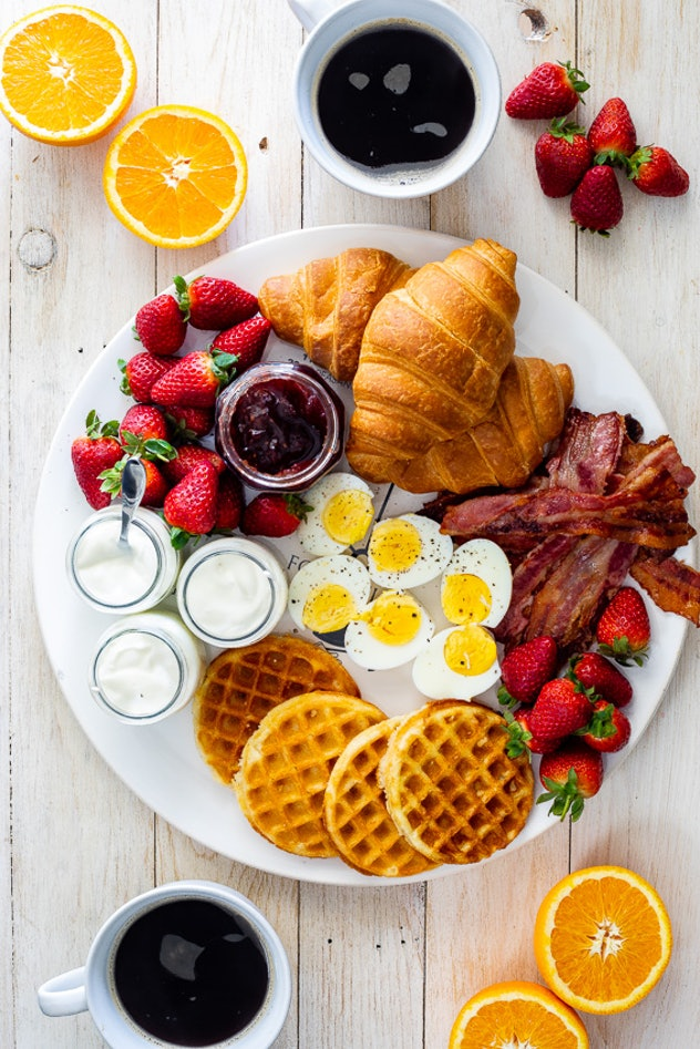 Tray of various breakfast foods including waffles, bacon, fruit, and eggs surrounded by cups of coffees and fresh sliced oranges
