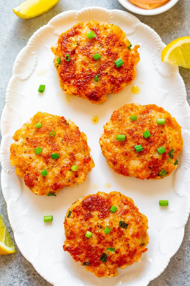 White plate with four shrimp cakes with green garnishes on top