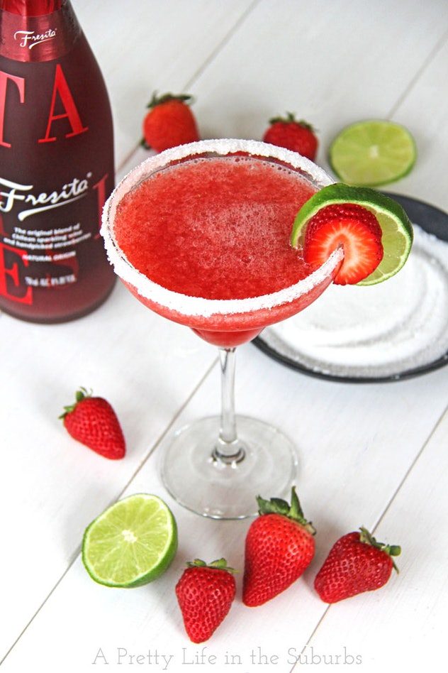 Margarita glass filled with strawberry wine slushie with fresh strawberries scattered at the bottom and a bottle of wine out of focus