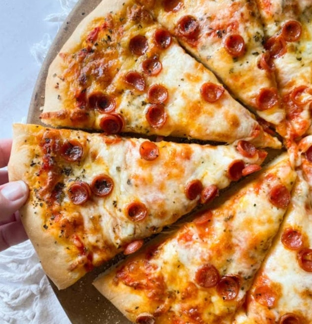 Baked pizza cut into triangles with a hand pulling one slice out