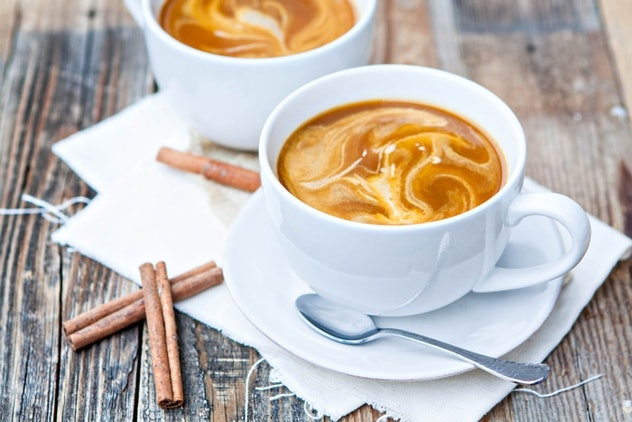 Two white mugs of caramel-colored coffee on white plates with spoons and cinnamon sticks surrounding them