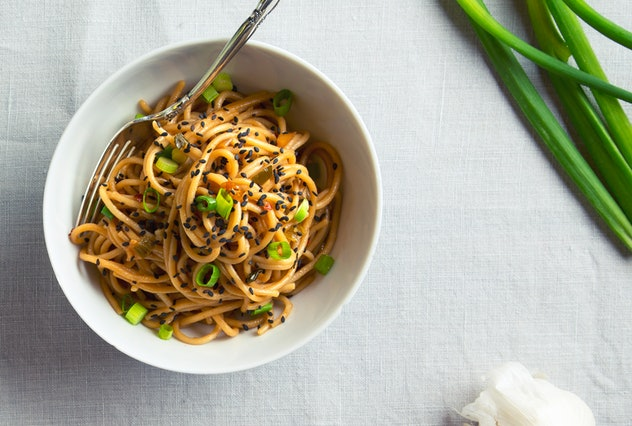 Bowl with noodles sitting on a table with a white linen tablecloth