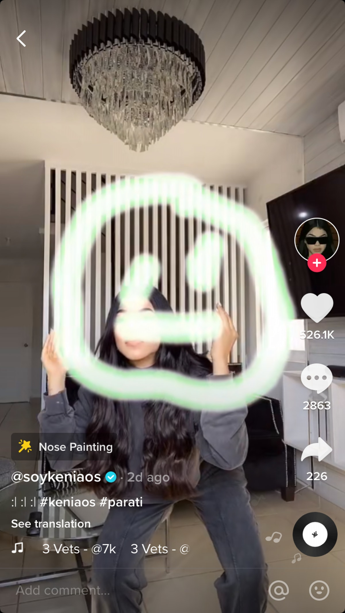 A woman draws a smiley face with her nose in her living room while doing a TikTok challenge.