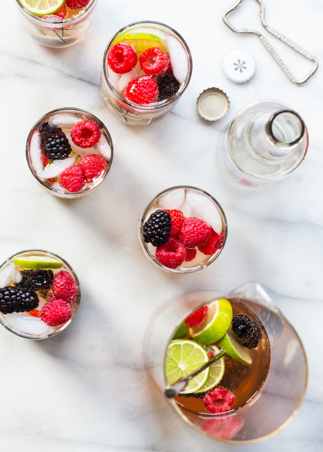 The top of several glasses full of sangria and topped with fresh limes, raspberries, and blackberries