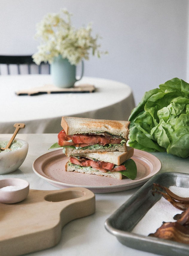 Counter top full of cookware and a white plate with halves of BLT stacked on top of each other