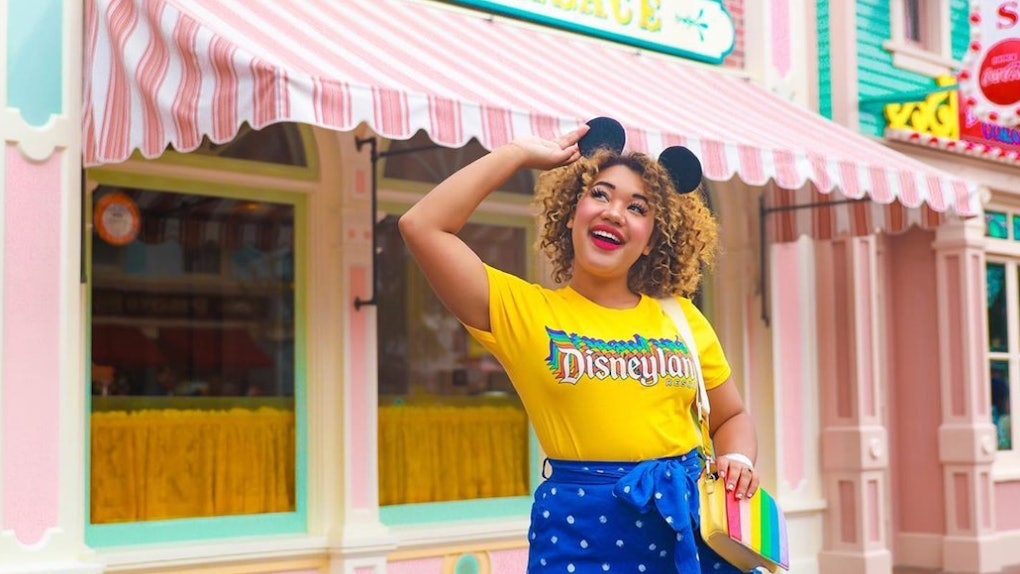 A happy woman with Mickey ears and a Disneyland shirt stands in the middle of Main Street at Disneyland.