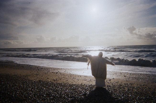 A bundled figure approaches the ocean.