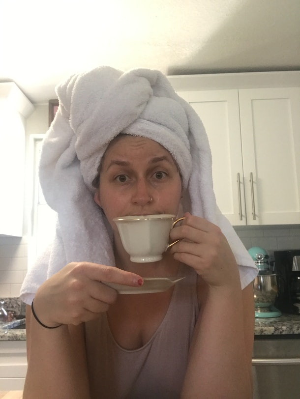 Rachel Varina (girl) with white towel on head drinks from white teacup.