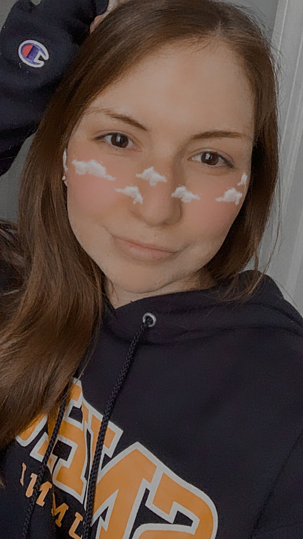 A young woman in a sweatshirt poses with an Instagram filter applied to her face.