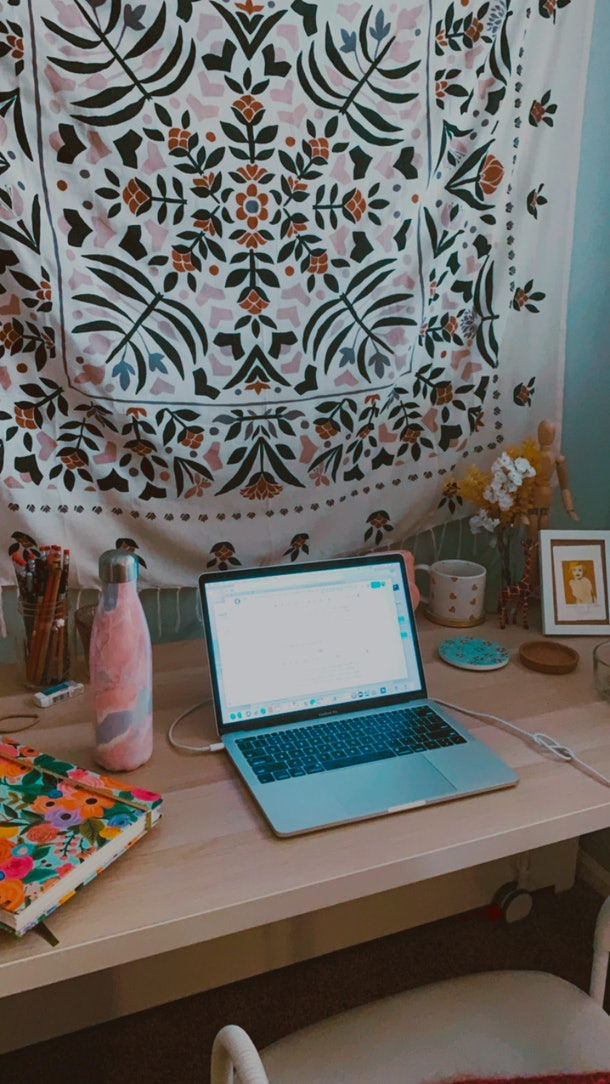 An office space is decked out with a tapestry, floral planner, and colorful water bottle.