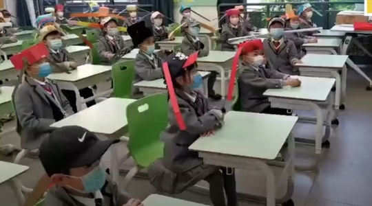 Kids are heading back to school in China and wearing homemade social distancing hats.
