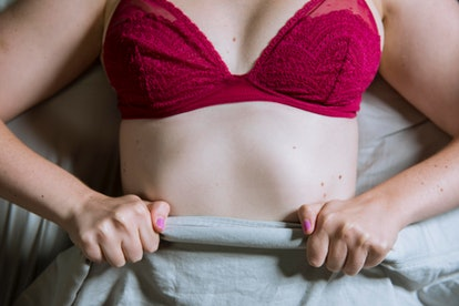 Woman gripping the bed sheets. Vaginal masturbation may take some practice.