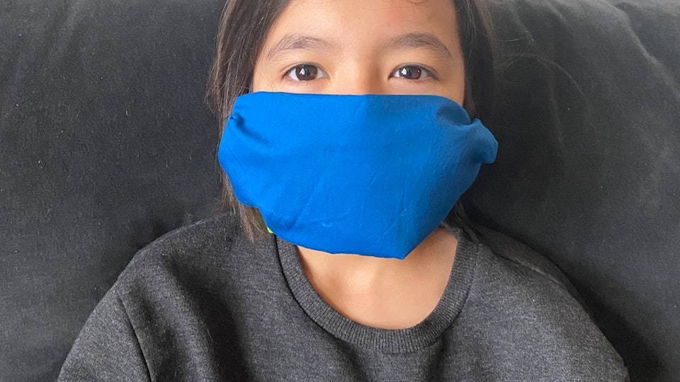 A cute girl in a turquoise face mask.