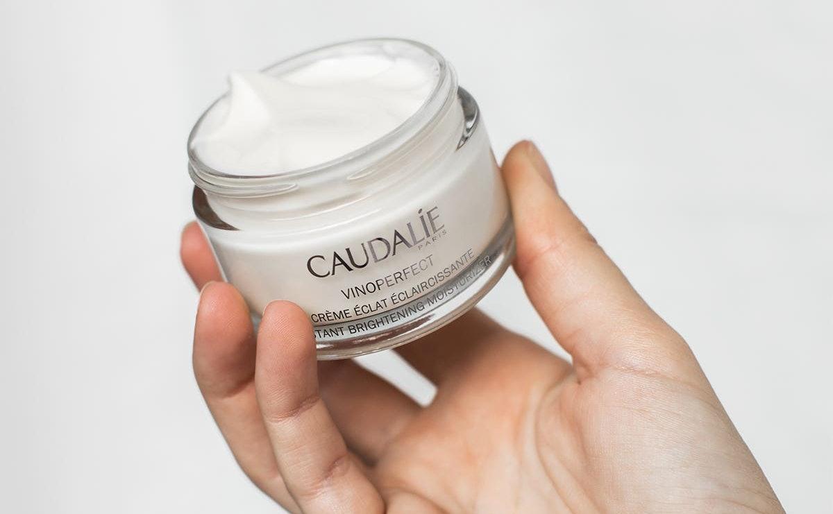 Caudalie's new Vinoperfect Instant Brightening Moisturizer with model.