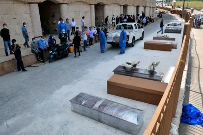People wait next to coffins and cardboard boxes to bury their loved ones outside a cemetery in Guaya...