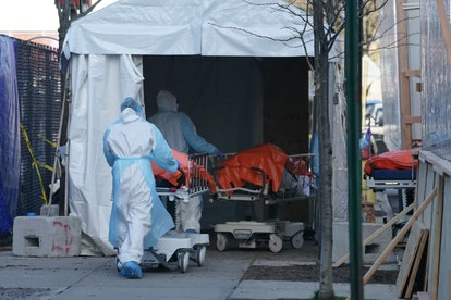 Bodies are moved to a refrigerated truck serving as a temporary morgue for Wyckoff Hospital, Brookly...