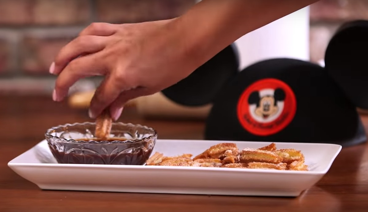 A woman's hand dips a Disney churro tot into chocolate sauce, with a Mickey Mouse hat in the background.