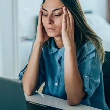 A person frowns as she rubs her temples, staring at her computer. Stress can impact your sleep, which can make you more stressed, which can impact your sleep; medical experts say that it's important to break this cycle to help keep your immune system healthy.