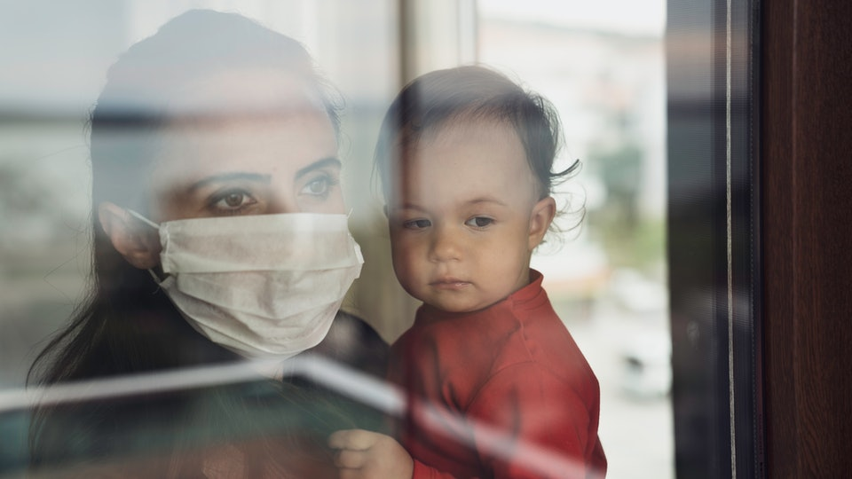 Mother in a protective facemask holds her child in front of a window