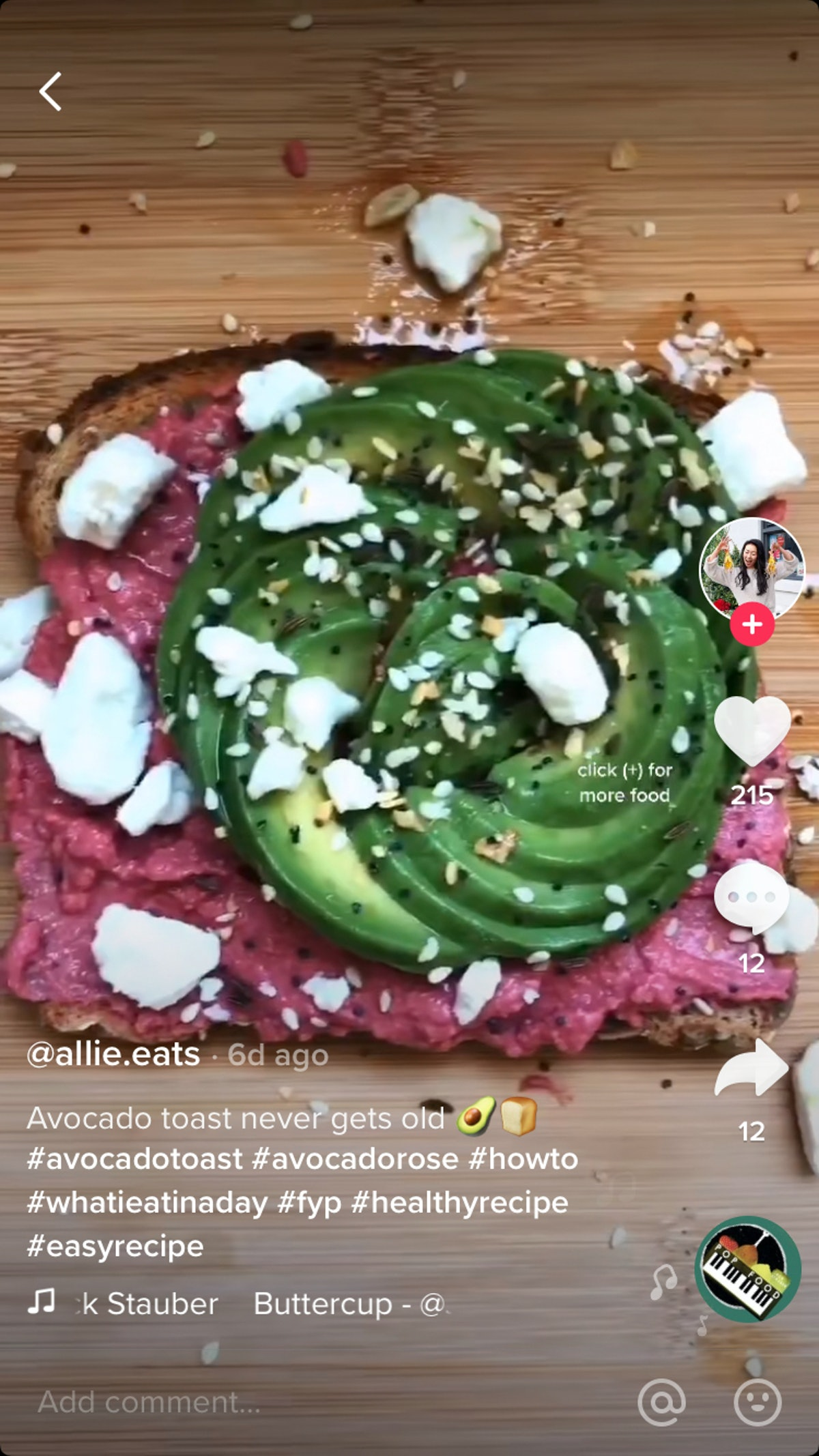 An avocado, shaped like a rose, sits on top of red beet hummus, with feta and bagel seeds sprinkled on top.