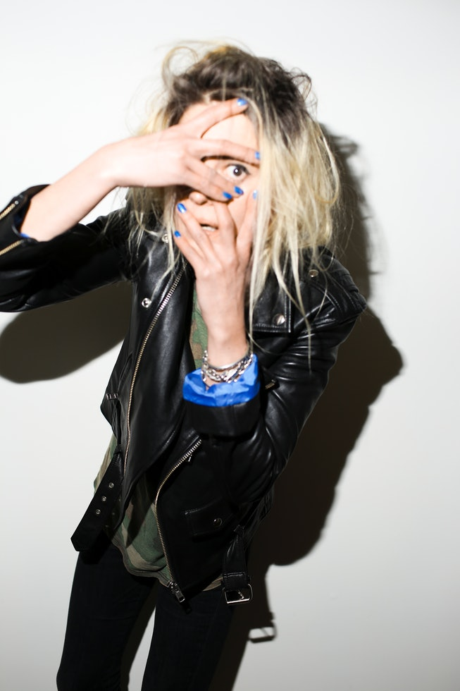 Alison Mosshart peers into the camera, her hand covering everything but her eye.