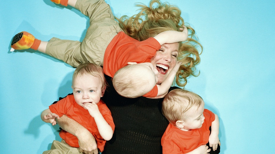 A woman surrounded by babies