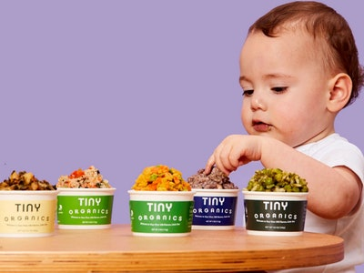 a baby looking at several containers of tiny organics baby food