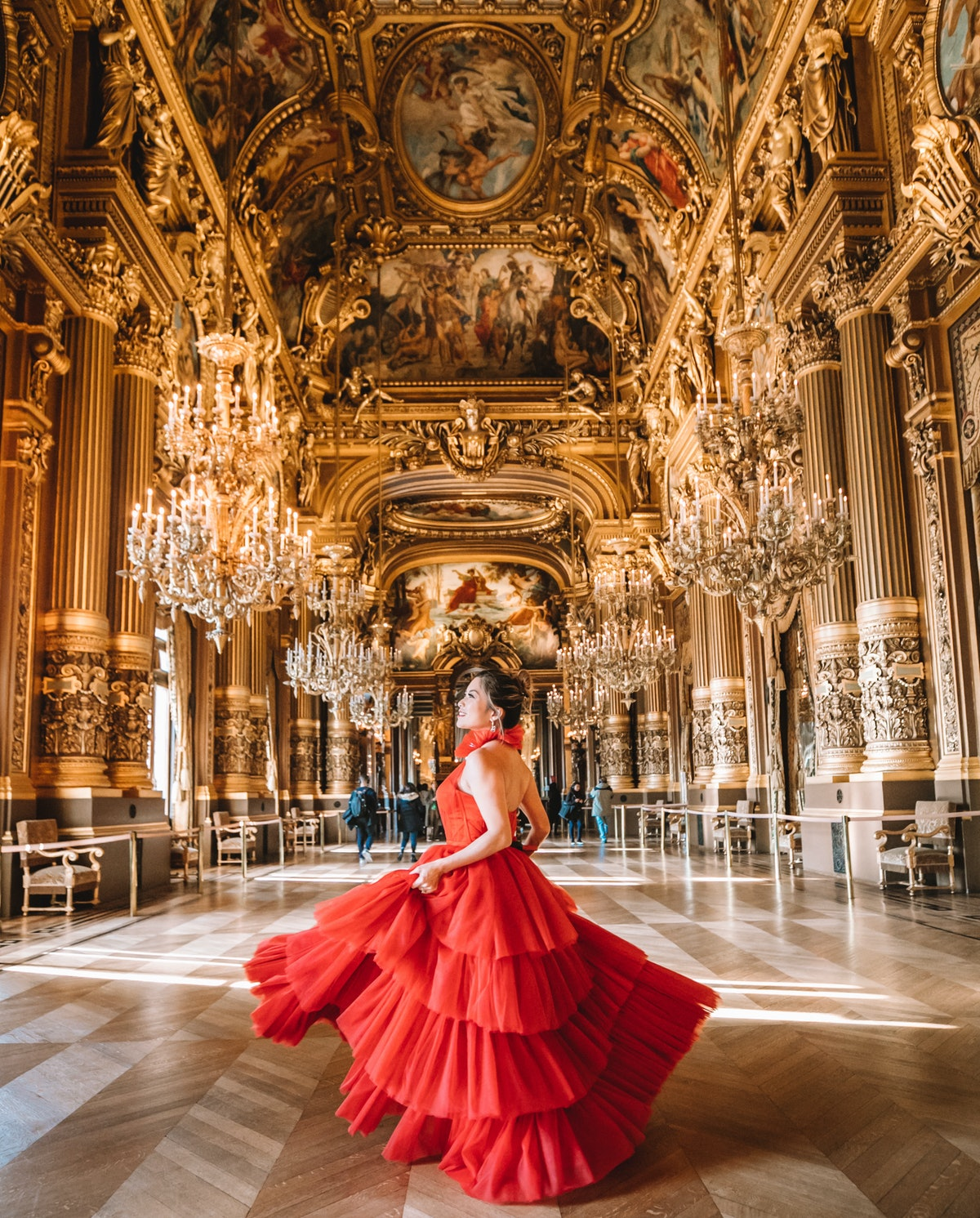 A woman in a red tulle gown twirls in an elegant ballroom.