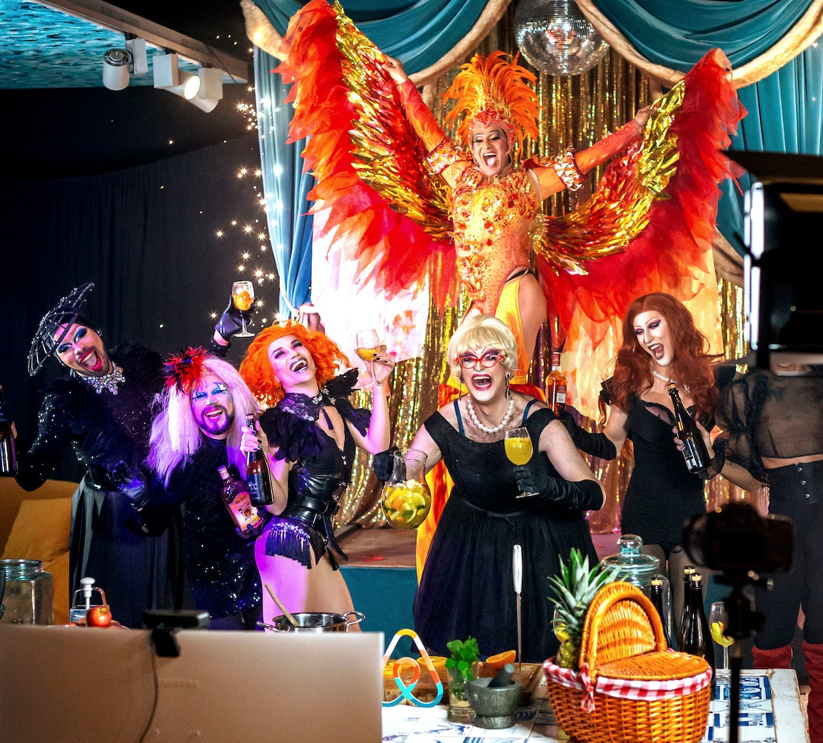A group of drag queens dance and hold glasses of sangria for a virtual show.