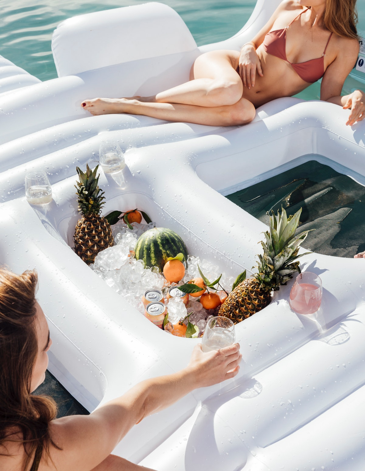 Two girls lounge on FUNBOY's Giant Dayclub pool float that has a cooler filled with drinks and fresh...