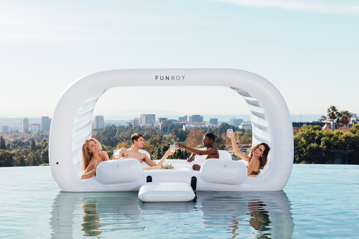 A group of friends hangs out on FUNBOY's Giant Dayclub pool float while in an infinity pool overlook...