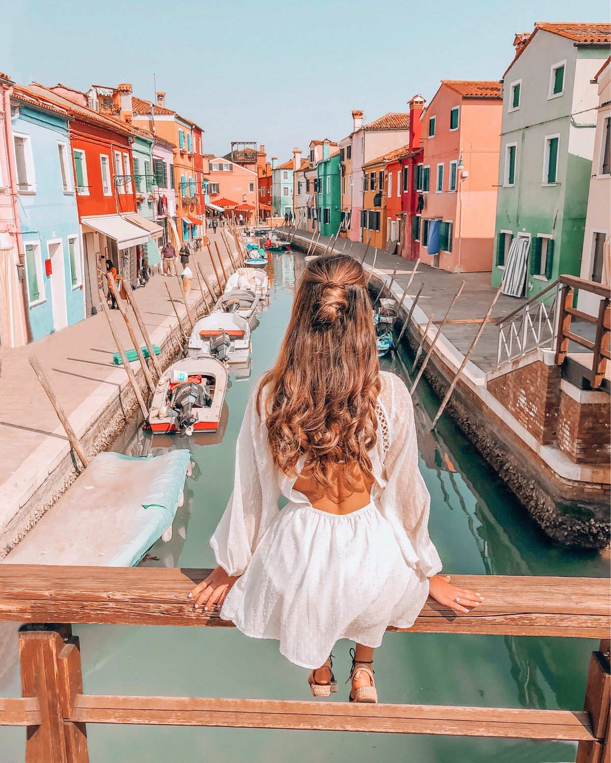 A brunette woman in a white sundress sits on a bridge overlooking a canal and colorful buildings in ...