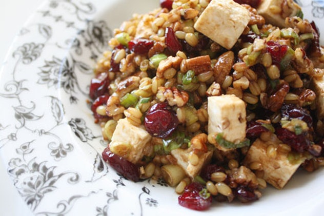 Plate with a pile of wheat berry salad featuring cranberries, pecans, green onions, and feta cheese