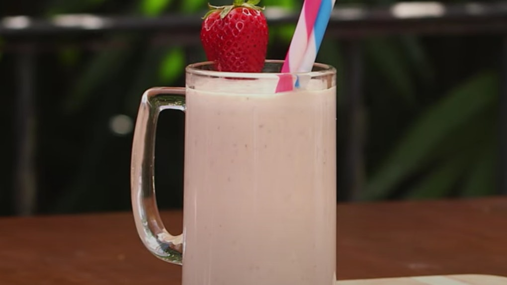 A mug filled with a peanut butter and jelly milkshake sits on a table with a strawberry decoration on the rim.