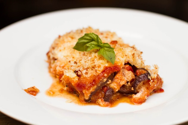 White plate featuring a slice of eggplant parm