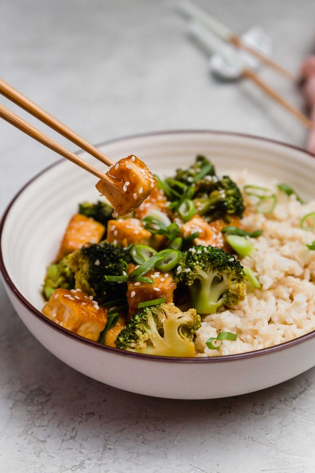 A bowl of savory broccoli and tofu with rich sauce and rice.
