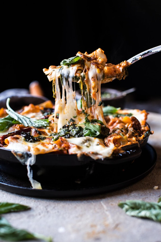 Iron skillet full of vegetarian skillet lasagna with a fork pulling out a chunk and hot cheese stringing