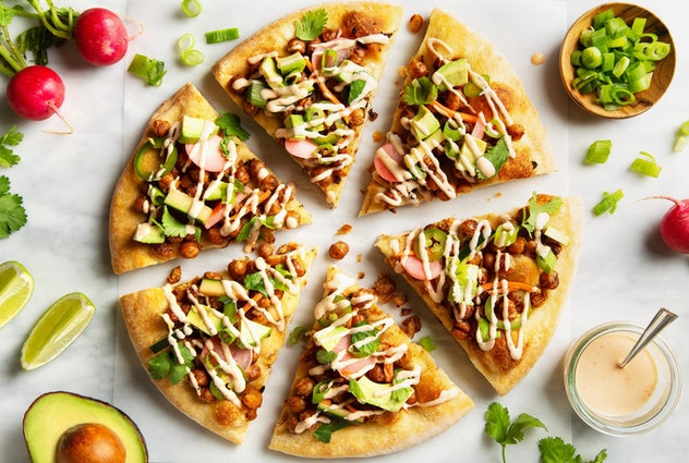 Pizza cut into six slices with avocados, lime slices, radishes, green onions, and a special sauce surrounding it